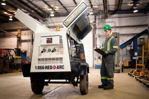 Worker checking equipment at Certified Mining & Construction Sales & Rentals