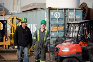 Two workers walking in yard at Certified Mining & Construction Sales & Rentals
